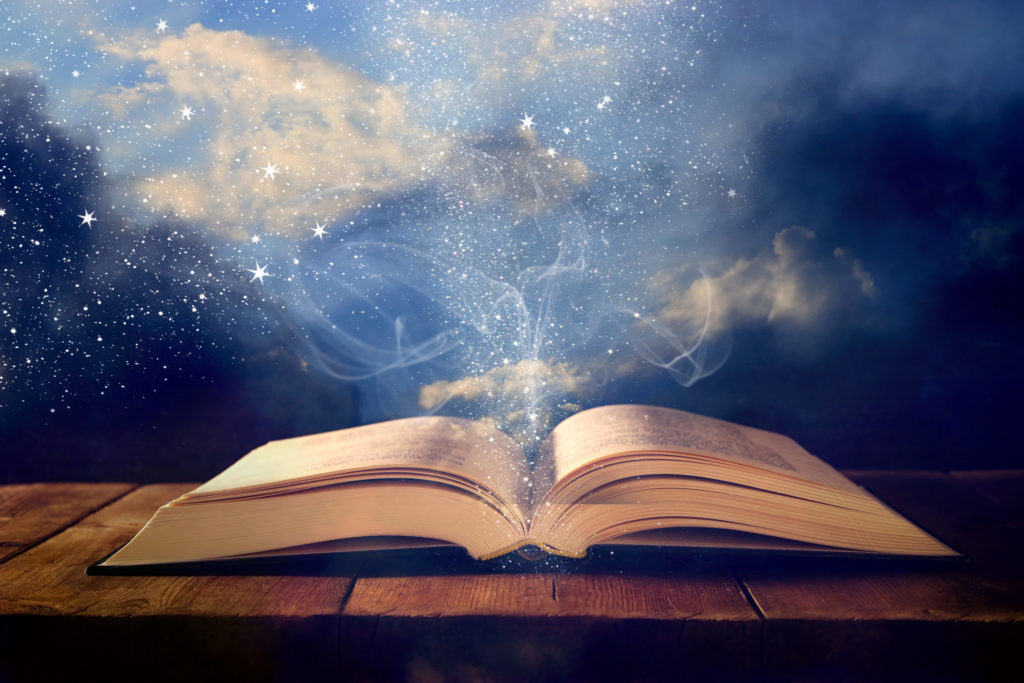 image of open book on wooden table with glitter overlay