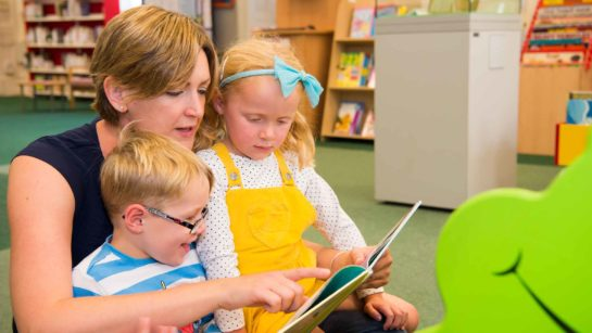 Children and their mother enjoy books in the Harris library