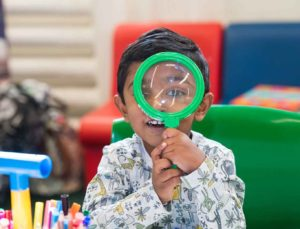 A boy uses a giant looking glass in the Harris library