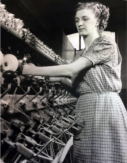Lady wokring in cotton factory, operating cotton reel machine.