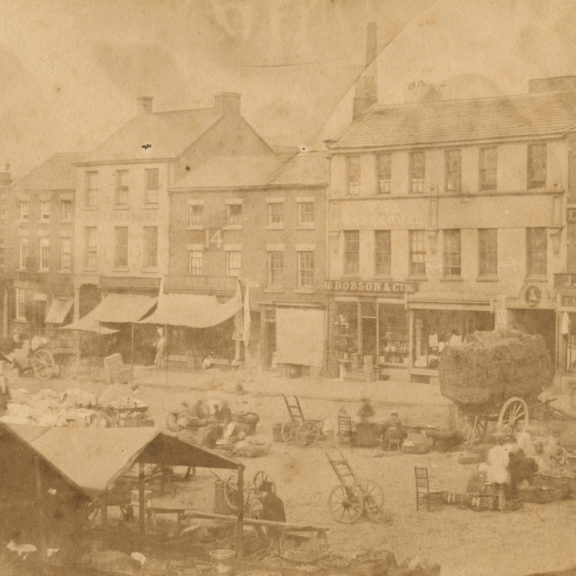 Images shows flag market as it was in 1853. The front of the Harris is where the row of shops is today. Old fashioned sepia image with stall holders and traders.