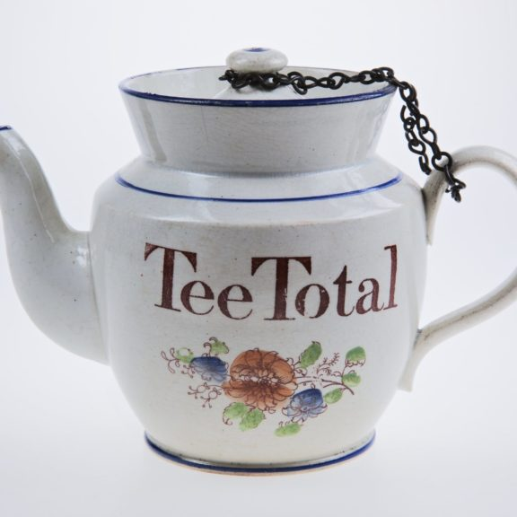 White tea pot with the words 'Tee Total' and decorative flowers on it.