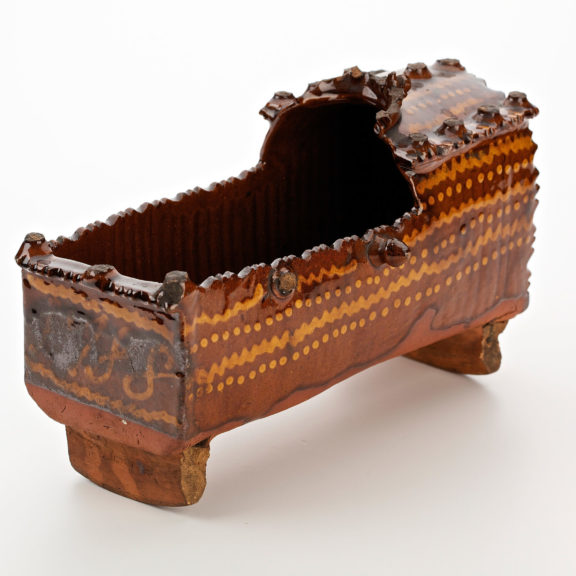 Small wooden cradle decorated with gold coloured dots