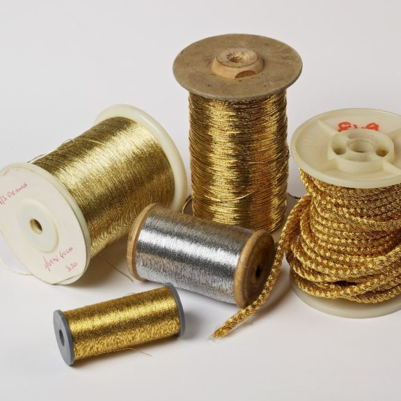5 cotton reels with golden thread on them.