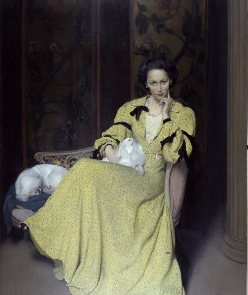 Lady sat in chair looking seductively in armchair with two small fluffy dogs. Lady is wearing long satin yellow dress.