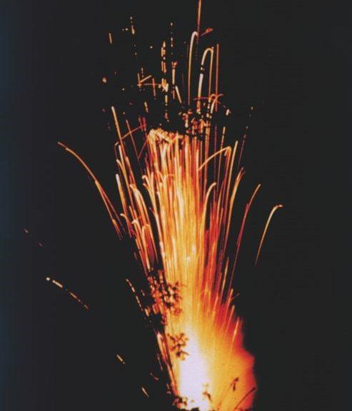 Meteorite sparking in bush in a forest. Dark background with bring orange light