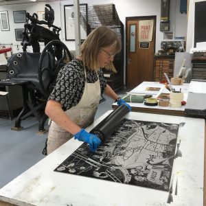 Image shows artist in a studio rolling over a lino print of the Ingol tea towel design.