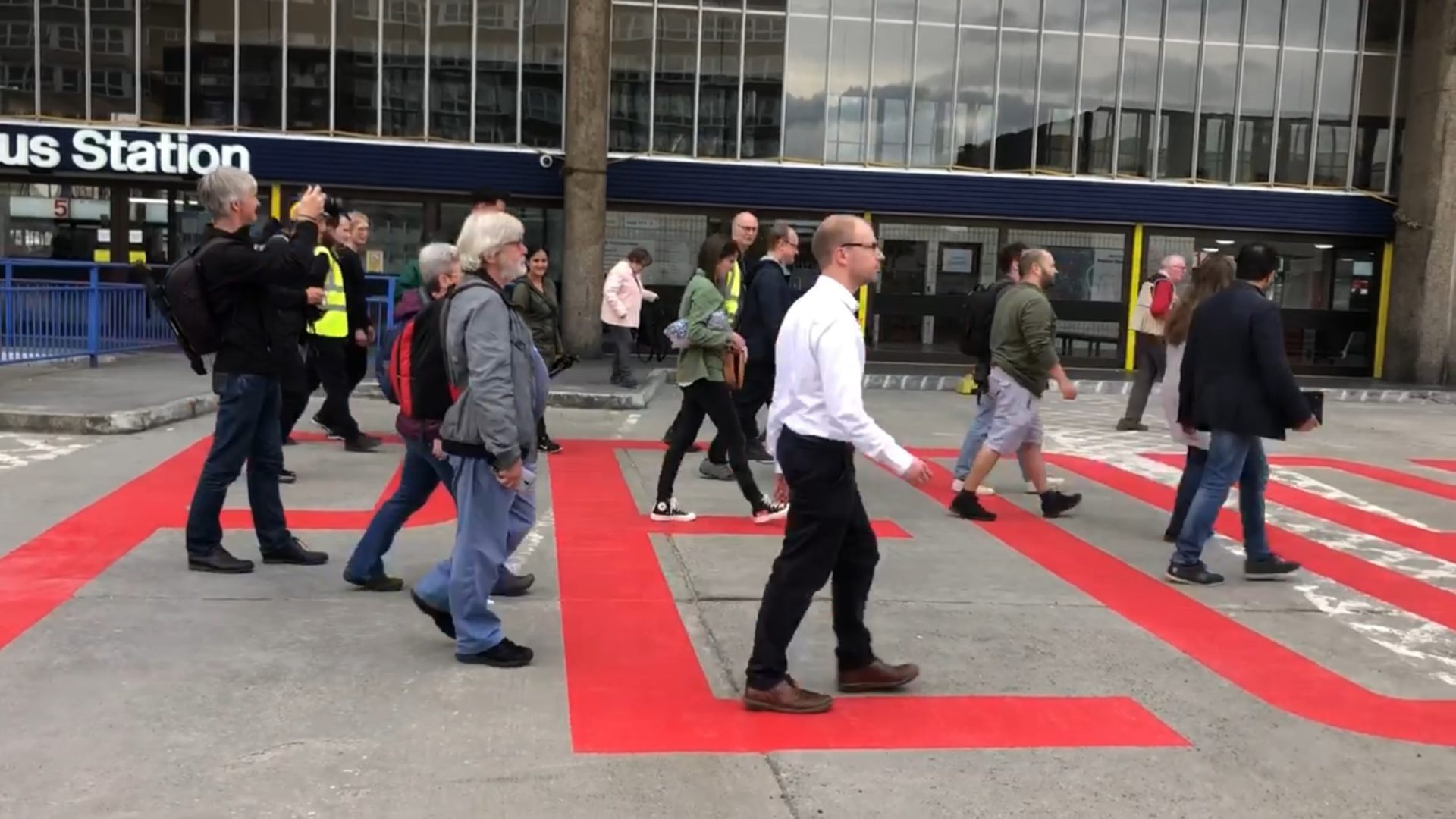 Image shows people walking over a large red sign that says 'People' painted on Preston bus station ground.