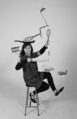 Image shows lady with different kitchen utensils balanced on her head arms and feet. She is sat on a stall and looks startled.