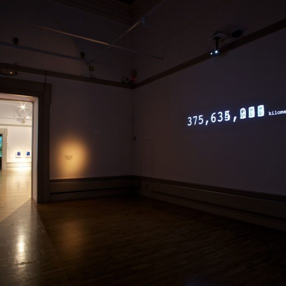 Darkened room with digital number 375,635 kilometers projected against wall in gallery