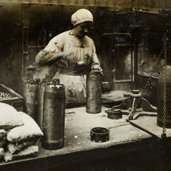 Lady working in factory filling metal shell that will be used for war.