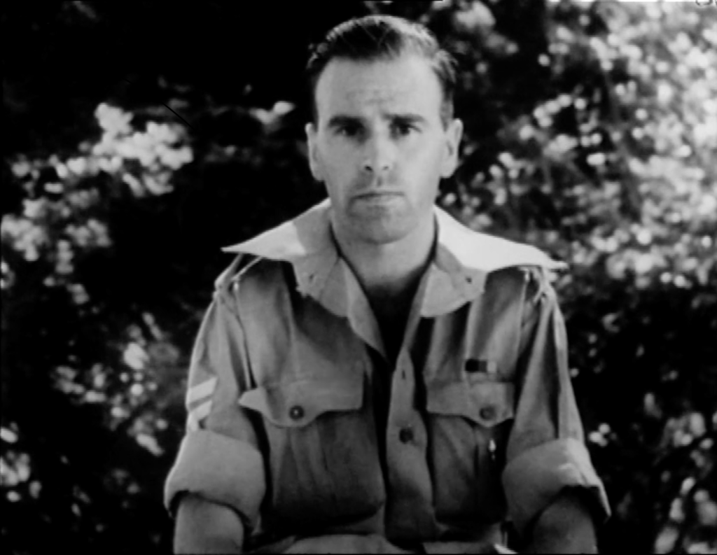 Man in army uniform speaking directly to camera. Black and white camera footage that links to full video once you click on it