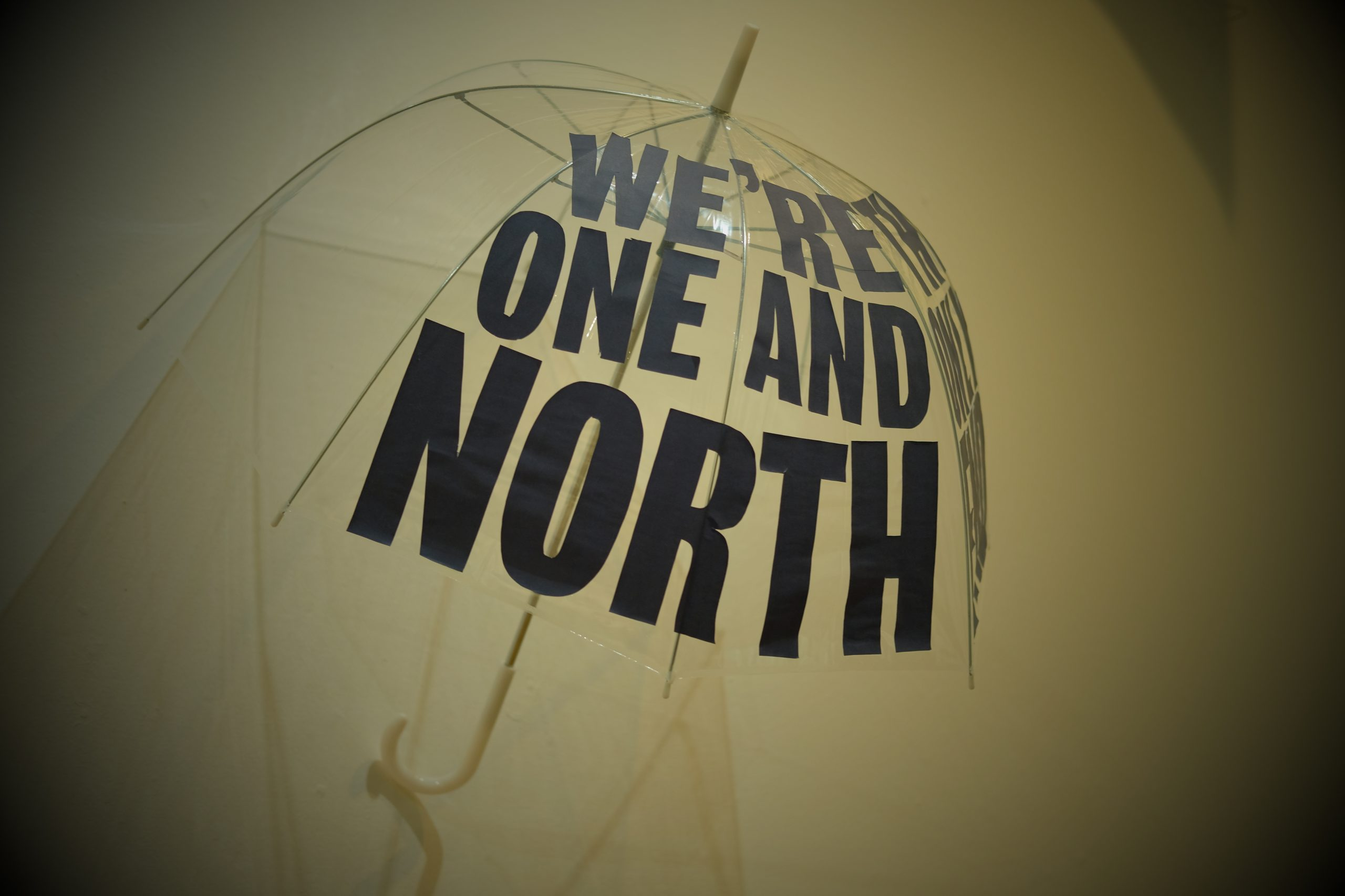 Umbrella with the words 'We're one and North' on it