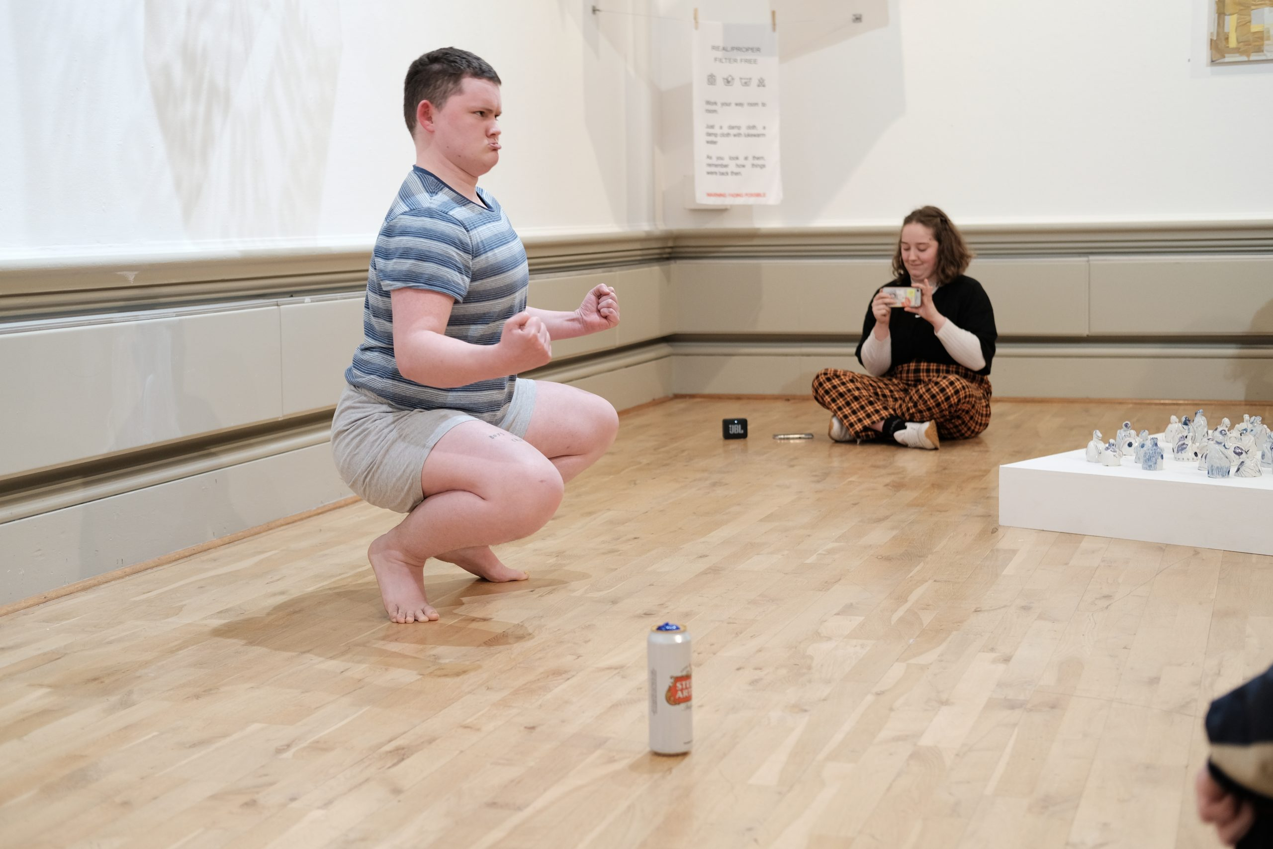 Image of Theo Seddon squating on the floor in the exhibition gallery, clenching his fists and performing part of his piece titled 'Dawn of Man'