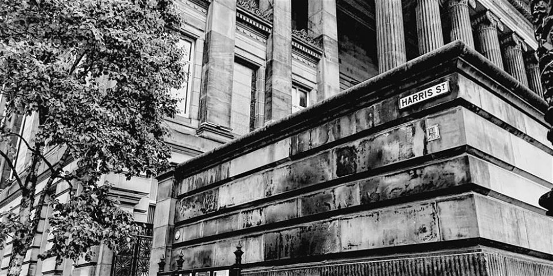 black and white image of the front corner of the harris building and road sign that says harris street