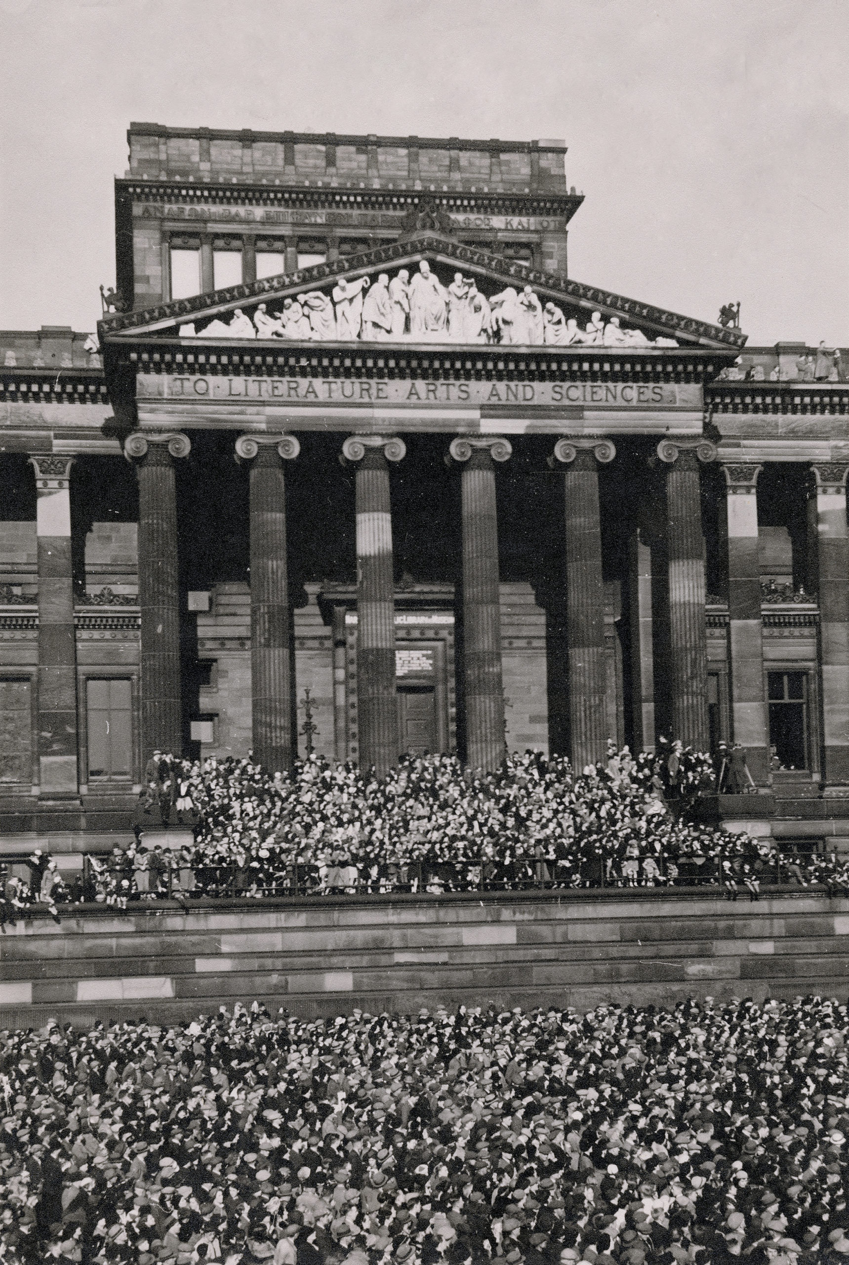 Old photo from the 40s of Preston flag market filled with a crows. Crowd is looking up at Harris Museum balcony which is also filled with people celebrating and listening to a speech