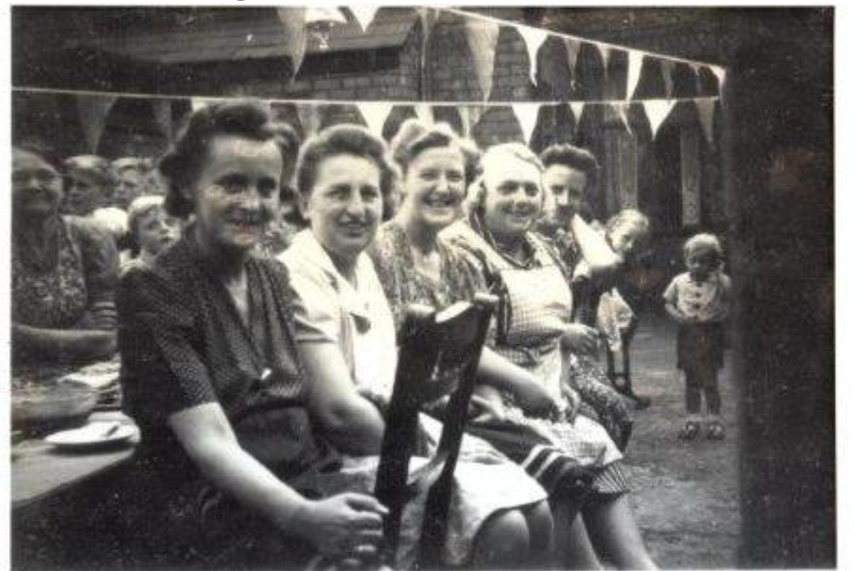 5 ladies at a streeth party with people behind them and bunting decoration overhead. There are 2 children in the background looking towards the camera. The ladies are smiling.