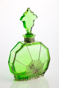 Green toilet water scent bottle with decorative metalwork in spiders web design