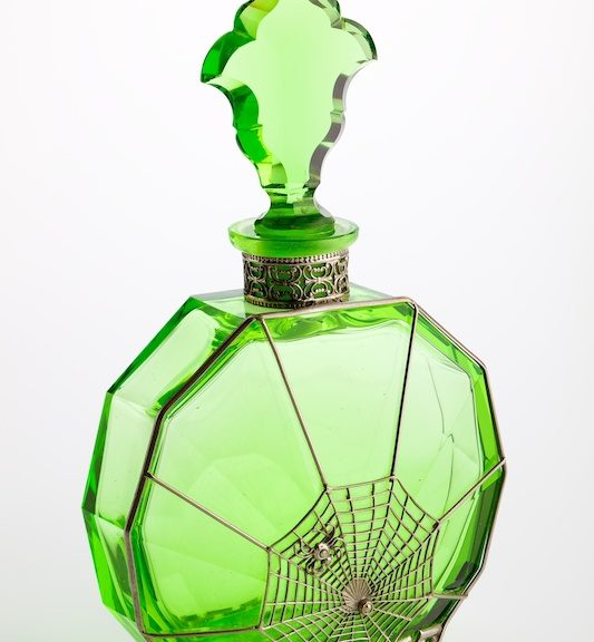 Green toilet water scent bottle with decative metalwork in spiders webb design