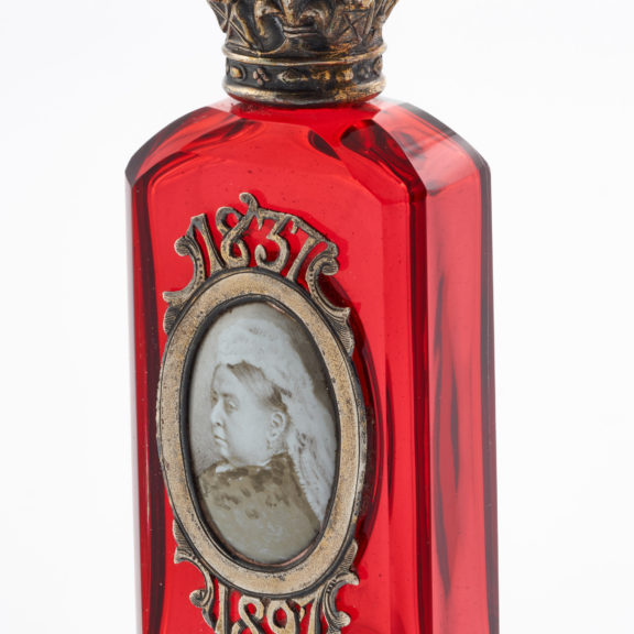 Red glass scent bottle with decorative crown shaped metal lid and image of Queen Victoria and dates 1837 and 1897