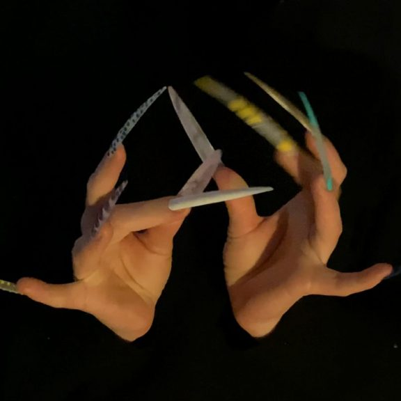 Two hands with very long pointed finger nails touching eachother in front of a black background