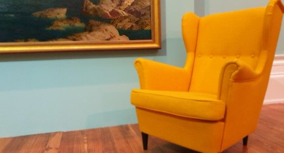 Yellow chair next to serene painting
