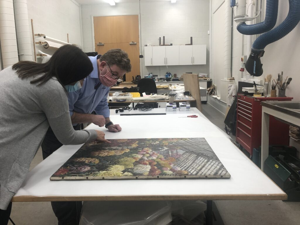 One of the Harris' curators at Lancashire Conservation Studio discussing a paintings restoration needs
