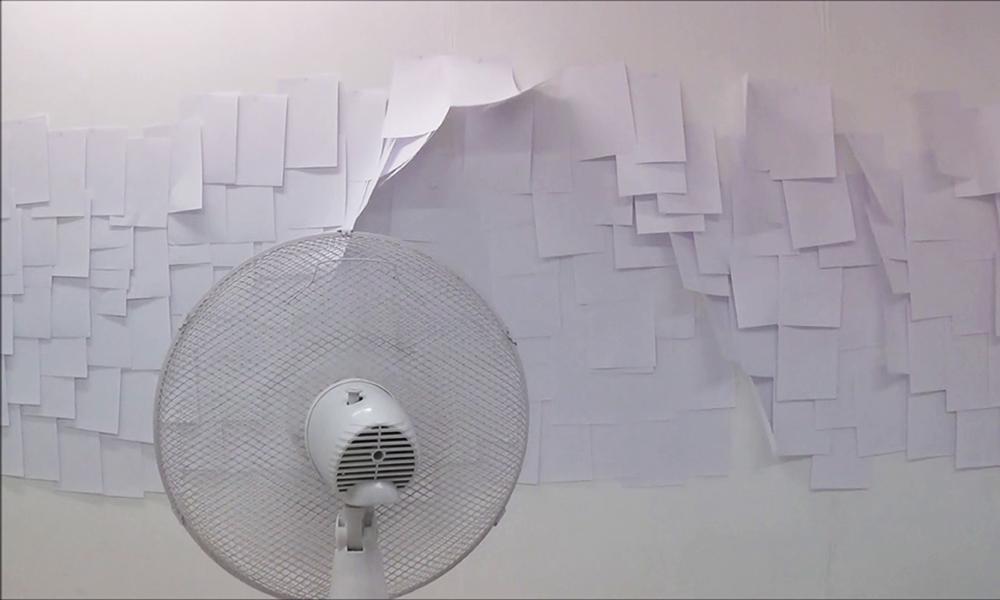 Fan blowing paper against a wall