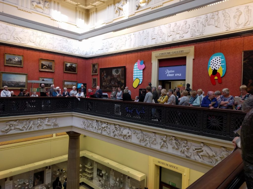 Large choir stood singing on second floor of Harris on Fine Art Balcony