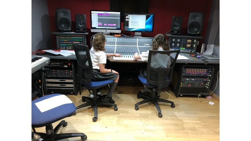 Two primary school aged girls sat at sound desk in recording studio ready to record their voice overs for final video piece.