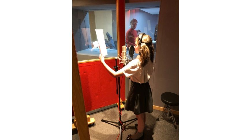 Primary school aged girl recording voice over in studio with head phones on.