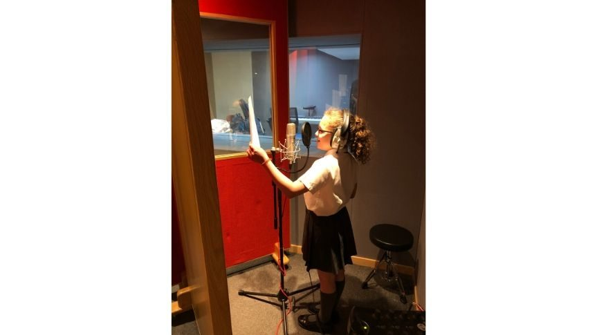 Second Primary school aged girl recording voice over in studio with head phones on.