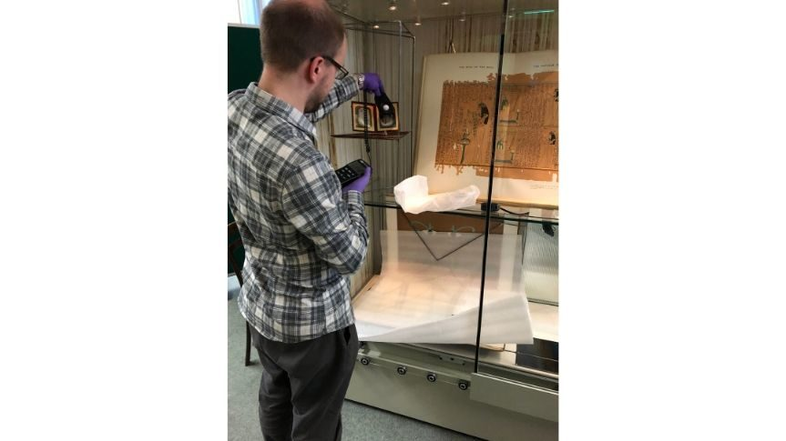 Photo of History Curator setting light levels in cabinet that houses daguerreotype and old Egyptian books. James is using a small electrical device to do this.