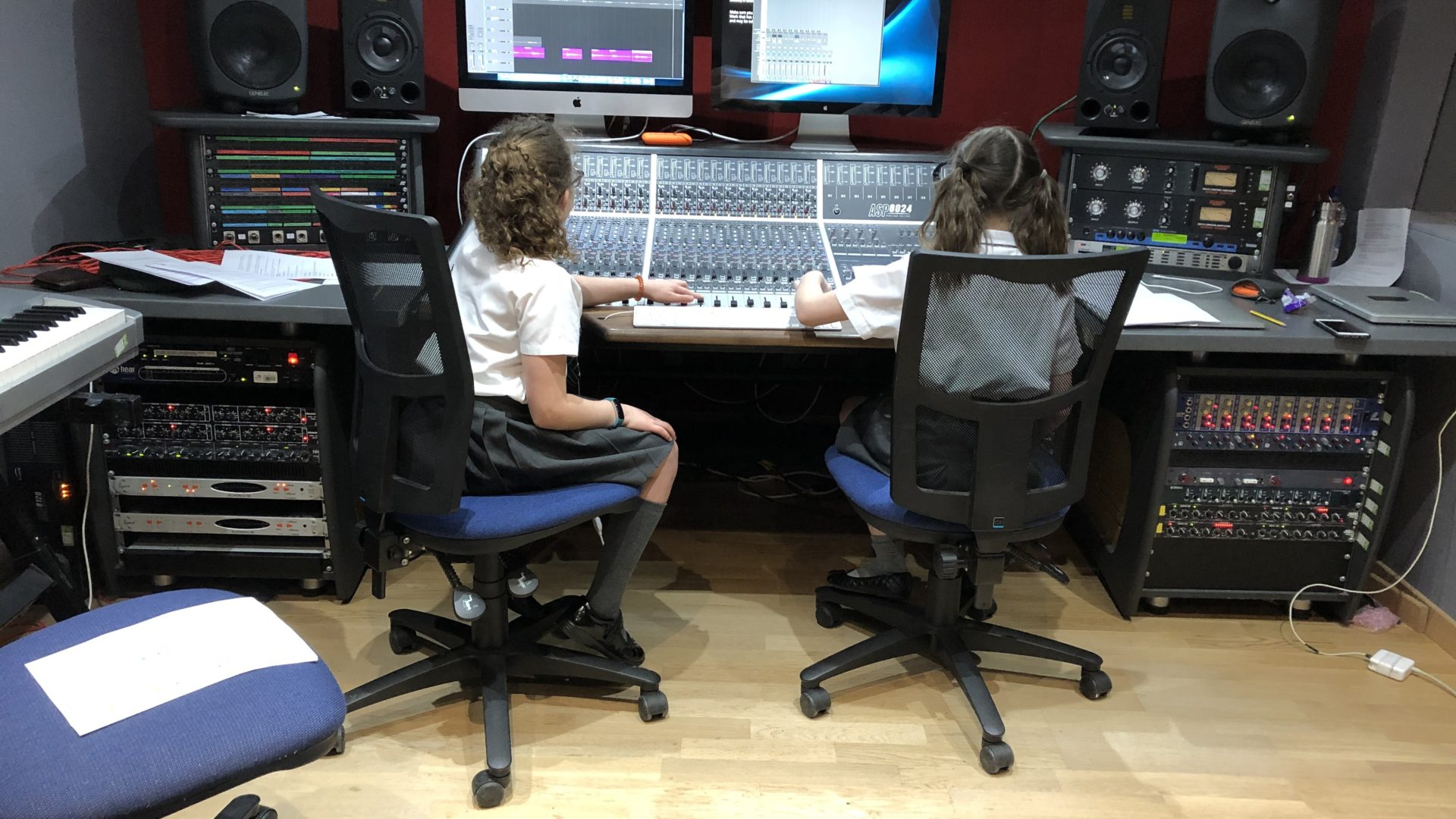two girls sat at sound desk in recording studio