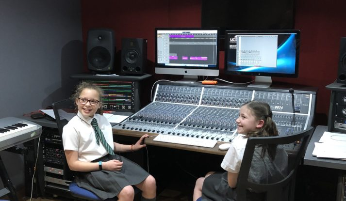 Two primary school aged children in a recording studio sat at a sound desk