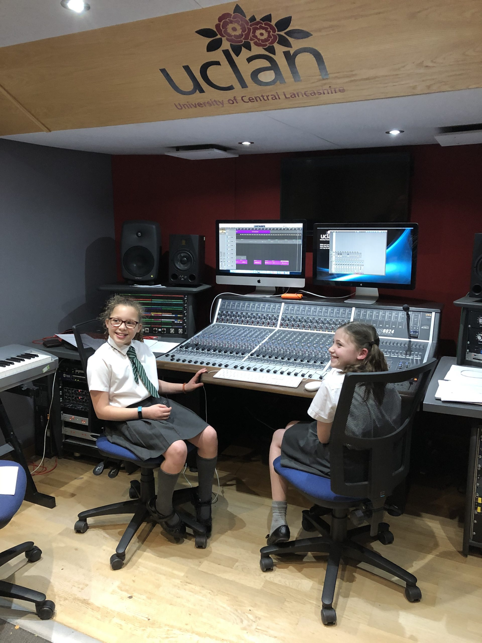 Two primary school aged children in a recording studio sat at a sound desk, smiling