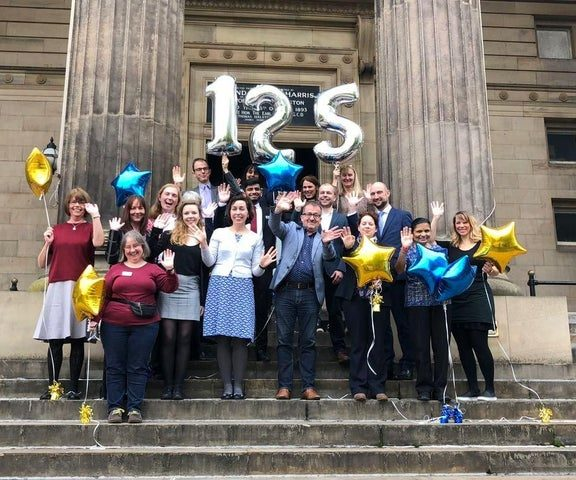 Staff stood on the front balcony of the Harris waving, holding 125 year balloons