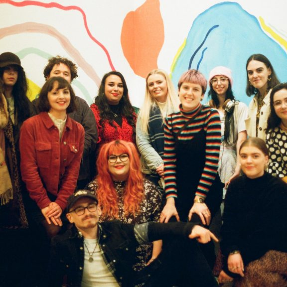 A group of young people in front of a contemporary artwork