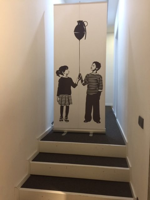 Photo of two children holding a balloon string together. There is a bomb attached to the top of the ballon string. Both children are looking up at the bomb floating above them. This illustration has been printed onto a roll up banner and photographed in this imaged.