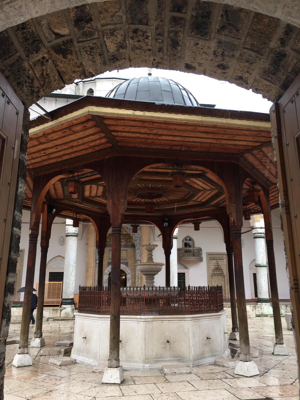 Photo of large structure with a domed roof. The supporting beams of the structure are made of wood with a fountain in the middle.