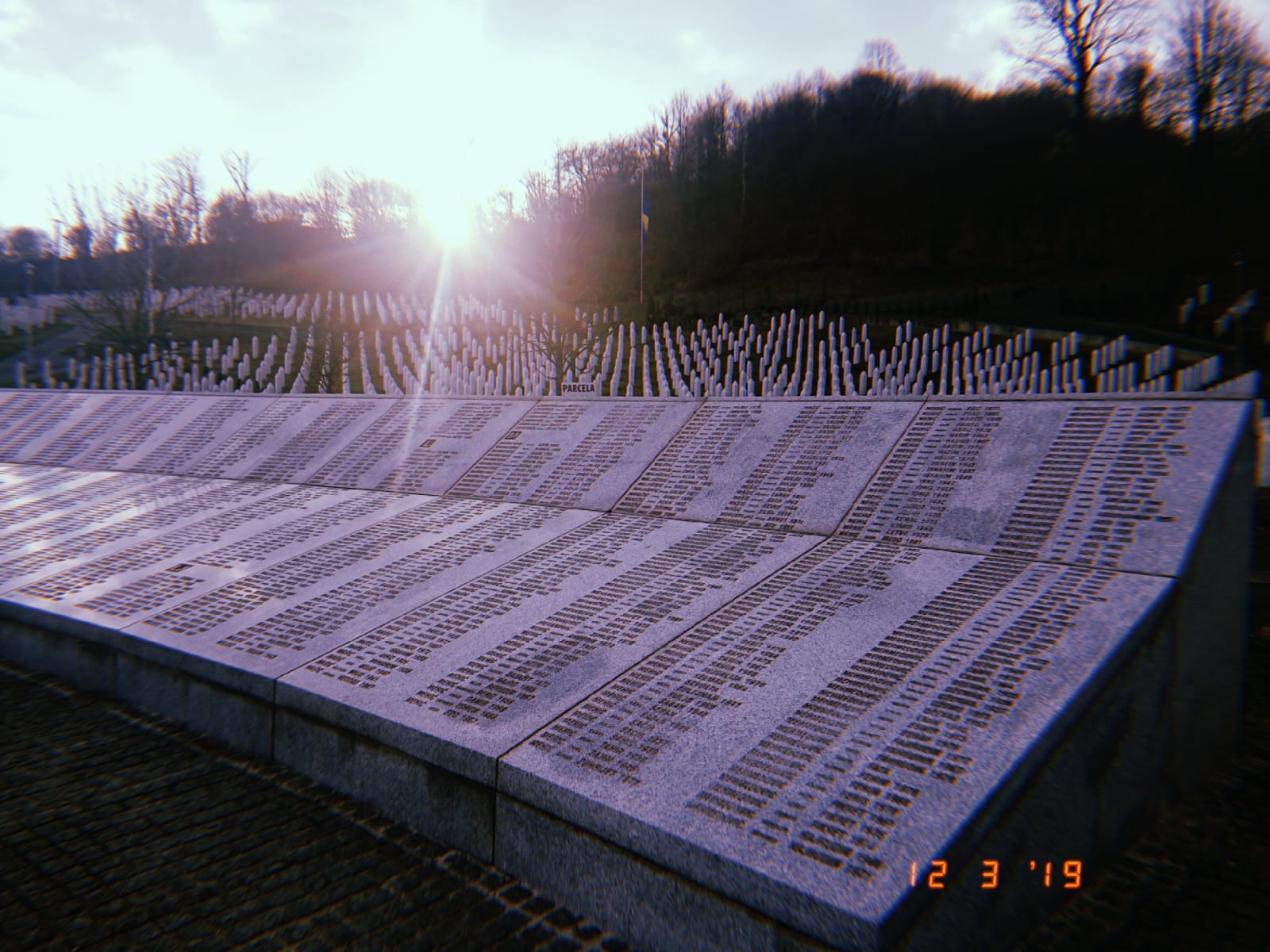 A long list of names of those who died in the Srebrenica Massacre listed on a stone structure. Behind the stone structure is a field with pointed tombstones spreading into the distance.