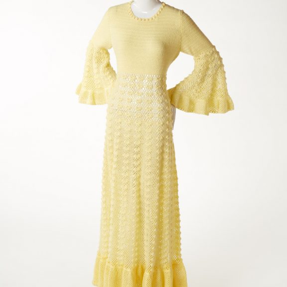 Mannequin wearing hand crocheted yellow full length evening dress with wide pagoda sleeves.