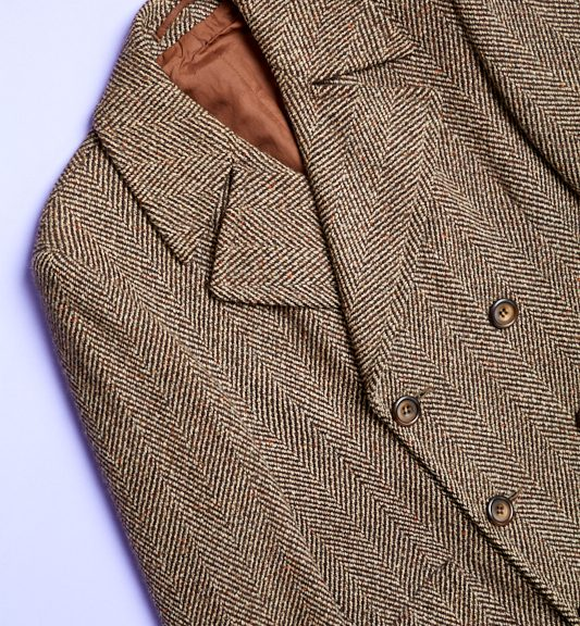 Gentleman's all wool herringbone overcoat, brown fabric with brown silk lining. Fastens with three buttons.
