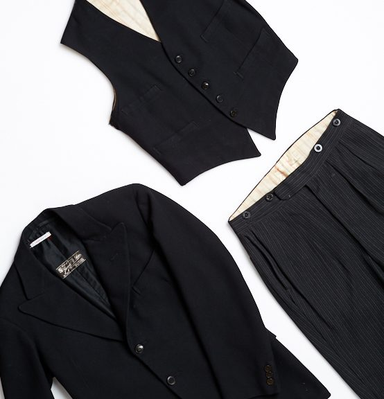 Image shows three flat pieces of a men's suit. Bottom left of image is a black wool suit jacket with single breast two button fastening and black lining. To the right is a pair of black and gray pin-striped trousers, button fly with buttons for braces. At the top of the image is a black wool waistcoat with cream striped cotton lining, it has a five buttoned fastening with four pockets.