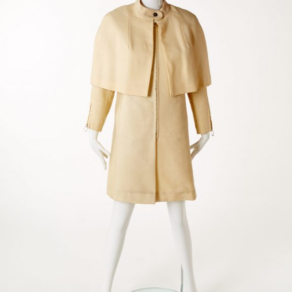 Mannequin wearing Mary Quant matching cream wool long sleeved coat and cape, coat has padded shoulders, a plain cape and a mandarin-style collar.
