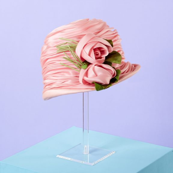 Pink hat, covered entirely in material that has been ruched and tucked. Two pink roses at the side made out of the same pink material, with green stems and leaves. Neat, bonnet-like hat with a small brim. Pink colour very vivid and sugary.