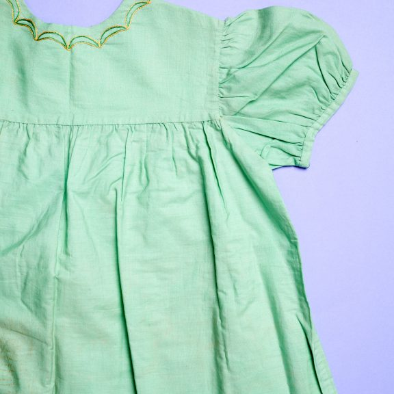 hild's dress, green cotton, with a high waist, full skirt, short puffed sleeves, buttoning at the bask with three white buttons, embroidered around the neck with a simple pattern of semi-circles in yellow and green silks