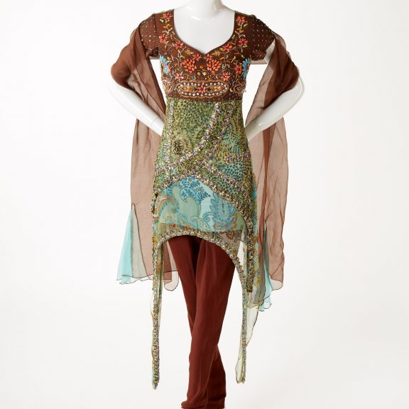 Mannequin wearing Kameez (top), churidar (trousers) and duppta (scarf) in brown and shades of blue, green, orange and purple with embroidered bead and sequin embellishment in a paisley and floral pattern.