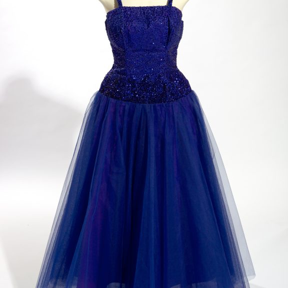 Image shows a deep blue evening dress, fitted boned bodice, shoulder straps, full skirt, dark blue nylon tulle over taffeta (man made), dark blue sequinned bodice on a white mannequin.
