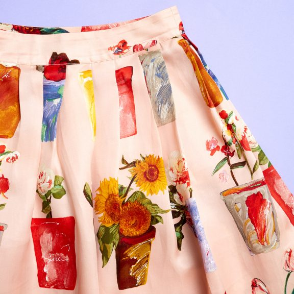 Image shows top right hand side of a Gucci skirt. The skirt is pink with different types of flowers in different colours and different types of plant pots. It is made of silk.